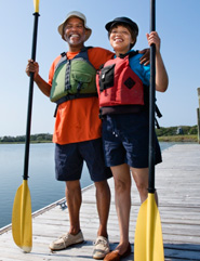 Mature couple standing on dock with canoe paddles and life jackets
